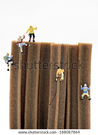 Miniature men climbing - stock photo