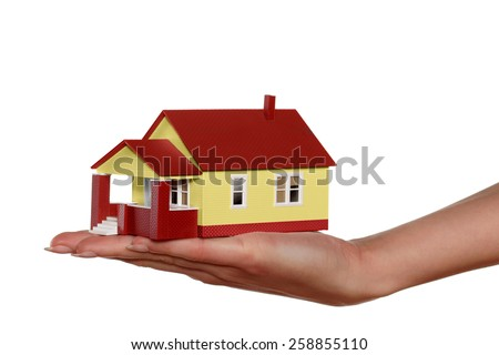 Miniature model house in woman's hand