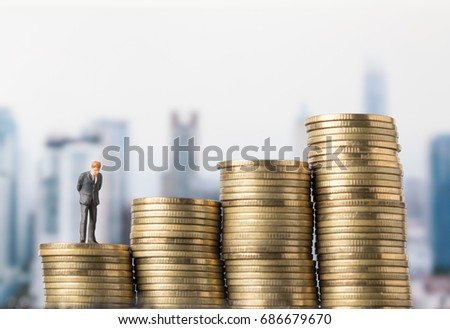 miniature model of investor standing on coin with city background. Business successful concept.