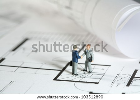 Miniature models of an architect and property owner shaking hands outside the building site of his new house - stock photo
