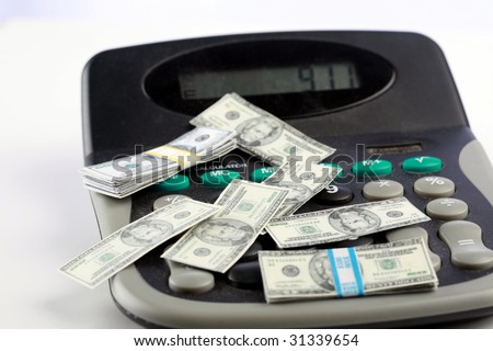 miniature money on a caluclator represents the world wide shrinking economy and inflation - stock photo
