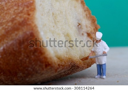 Miniature of a chef with bread on a wooden cutting board