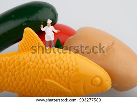 miniature of a chef with fish and vegetables