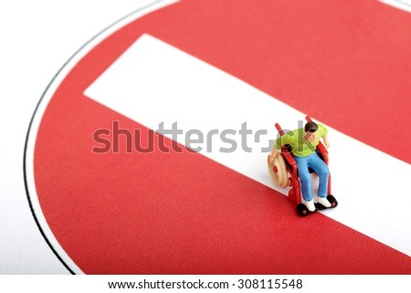 miniature of a disabled man on a wheelchair standing over a no entry sign - stock photo