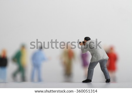 Miniature of a street photographer taking pictures of strangers walking on a white background - stock photo