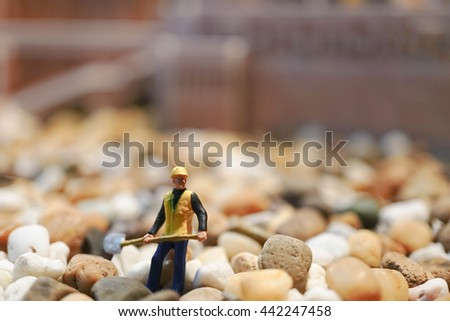 Miniature of construction worker is working on the construction site. Construction and work concept. SOFT FOCUS. Toned photo - stock photo