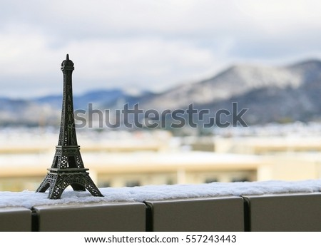 MIniature of Eiffel tower placed  on the wall in a  snowy day