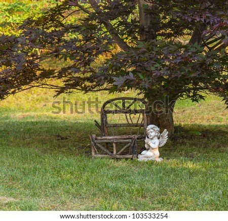 Miniature outdoor wooden bench, angel sitting along side. - stock photo