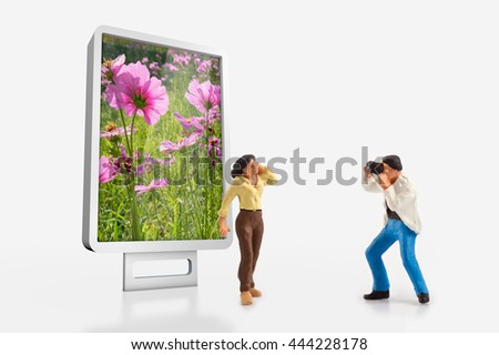 miniature people  - a photographer shooting a top model in front a billboard - stock photo