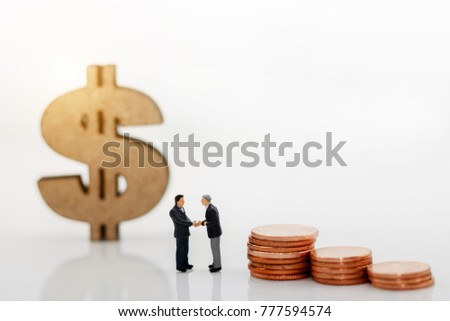 Miniature people: Businessman handshake with coins and dollar sign.  Investment, agreement, partnership and business concept