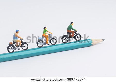 Miniature people cycling on pencil - stock photo