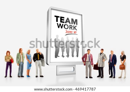 Miniature people in front a billboard about team work
