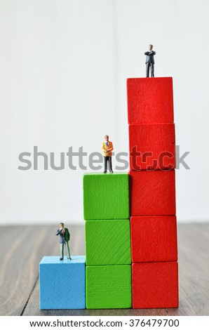 Miniature people on stack of colorful wooden cube building blocks - stock photo