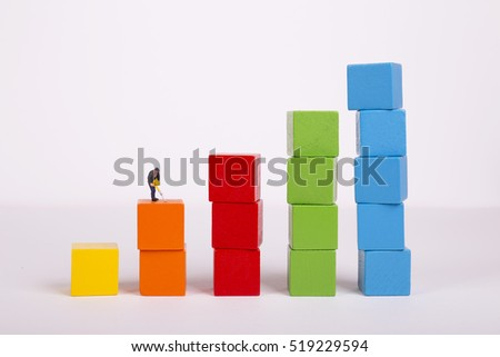 Miniature people on stack of colorful wooden cube building blocks, worker digging on colorful wooden cube.
