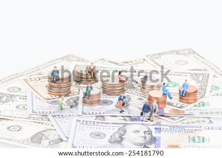 Miniature people on the coins and banknotes close up - stock photo