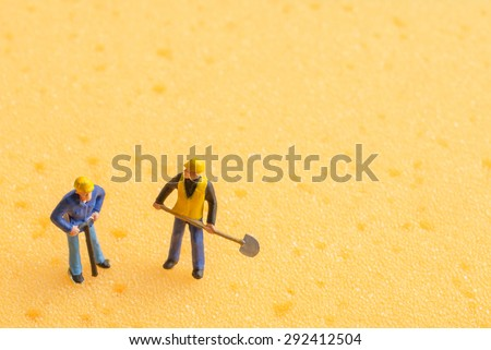 miniature people on yellow sponge background - stock photo