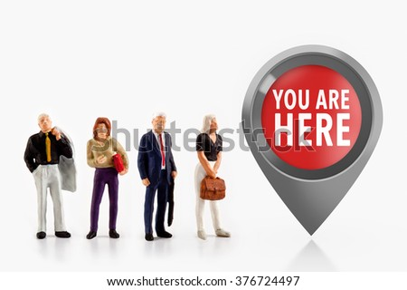 miniature people  - people stand in front the sign you are here