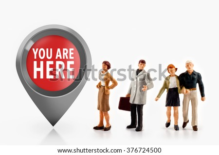 miniature people  - people stand in front the sign you are here - stock photo
