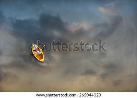Miniature people with paddle boat in a water reflection beautiful sunset - stock photo