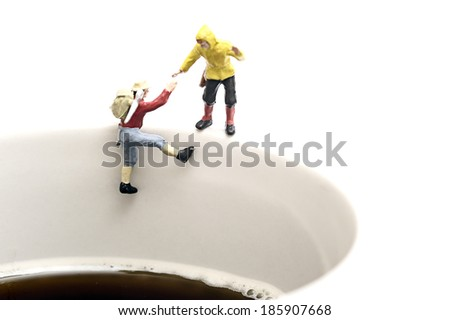 Miniature peoples climb up from coffee cup - stock photo