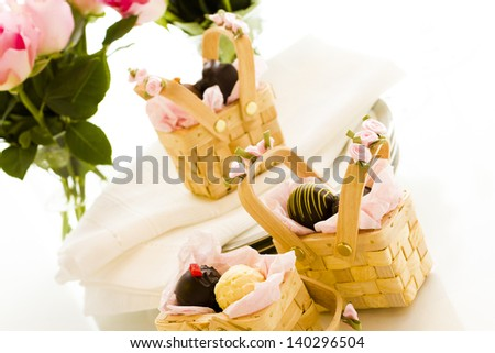 Miniature picnic baskets favor boxes filled with truffles. - stock photo