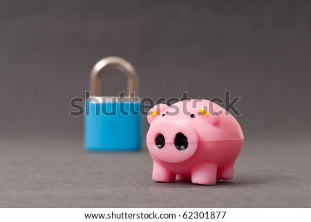 Miniature Piggy with Out of Focus Lock in Background ( Financial Security ) - stock photo