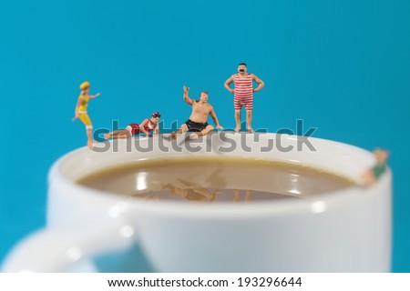 Miniature Plastic People Swimming in Coffee - stock photo