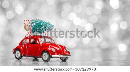 Miniature red car with fir tree on abstract background - stock photo