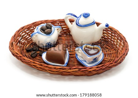 Miniature service for coffee, coffee beans and chocolate hearts in a wicker tray isolated on white background - stock photo