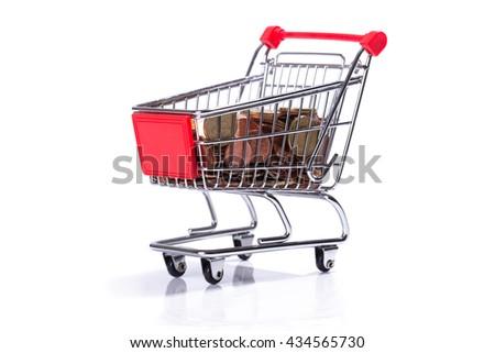 Miniature shopping cart with Euro money, isolated on white background - stock photo
