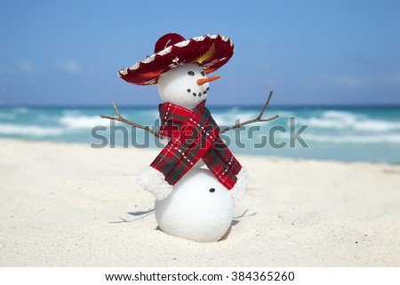 Miniature snowman wearing Mexican sombrero and scarf on the beach in Cancun