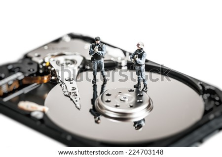 Miniature soldiers protecting computer hard drive. Technology concept. - stock photo