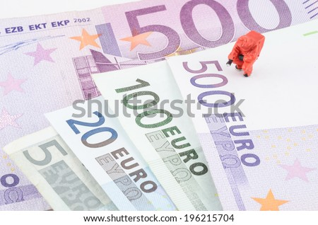 miniature specialist checking the counterfeit money - stock photo