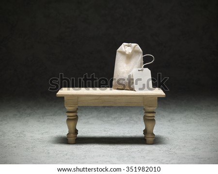 miniature table with a tea bag on dark background - stock photo