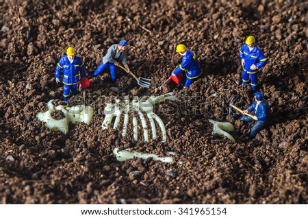 miniature technical team found the big human skeleton  - stock photo