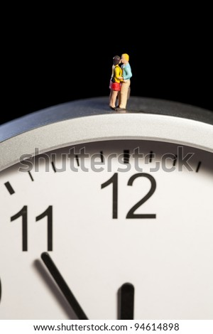 Miniature toy figurines of a young couple in a romantic embrace are balanced on the top of a clock showing five minutes to midnight. - stock photo