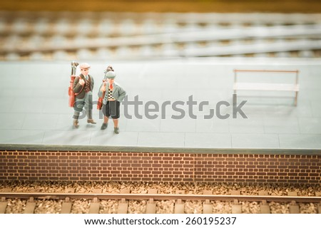 miniature train set figures on a station platform with golf clubs