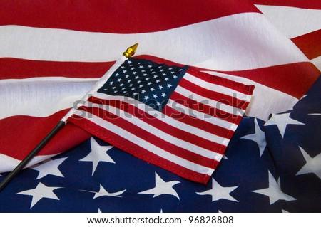 Miniature United States flag on larger flag - stock photo