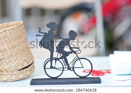 Miniature with 2 children on bike on wedding table. Wedding decoration with small girl a boy on bicycle. Vintage decor. Wedding decor idea. - stock photo