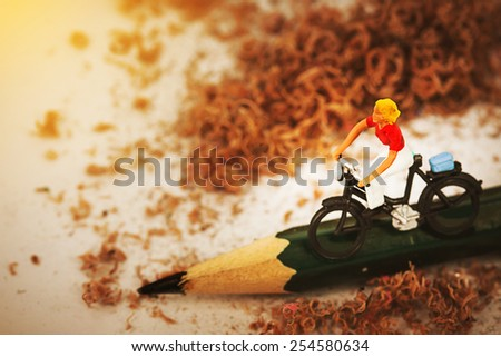 Miniature woman traveling on vintage bicycles along green pencil with sunset lighting . Macro photography,vintage color tone. - stock photo