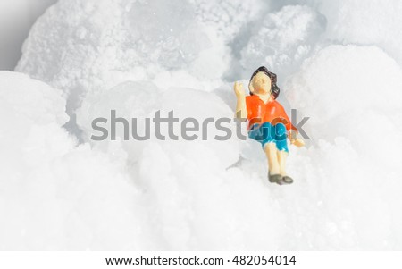 Miniature woman with small stone ice nature. concept freeze ice winter day