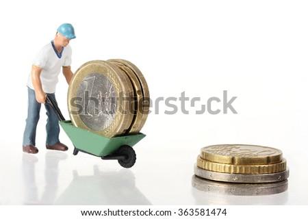 Miniature worker drives euro coins in wheelbarrow - stock photo