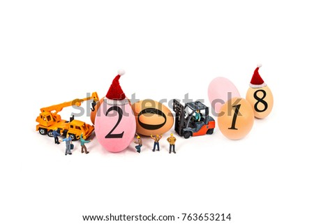 miniature worker team building standing front of forklift and truck with egg and 2018 number , on white background.abstract background to Happy new year decoration 2018 concept.