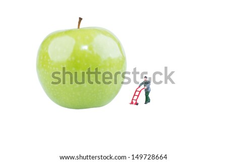 Miniature worker with sack barrow walking towards the fresh green apple - stock photo