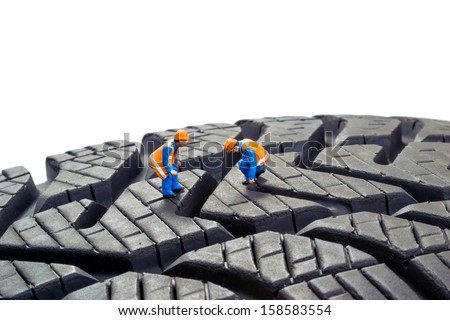 Miniature workers checking the depth tread on a car tyre - stock photo