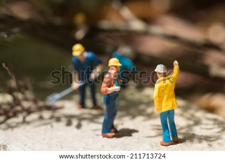Miniature workers taking a break in clearing the  fallen trees - stock photo