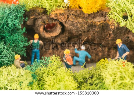 Miniature workmen clearing a pathway close up - stock photo