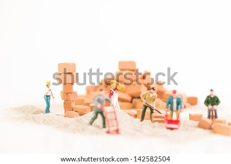 Miniature workmen working together doing construction brickwork - stock photo