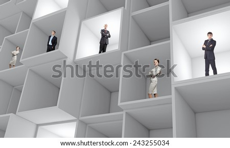 Miniatures of business people standing in cube