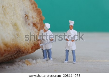 miniatures of cooks with bread on a wooden cutting board
